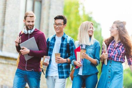Portrait de sourire étudiants multiethniques avec sacs à dos, marche dans le parc