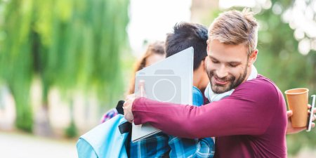 partial view of multicultural students with digital devices hugging in park