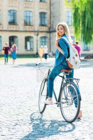 selective focus smiling young student with backpack on bicycle looking at camera on street