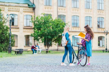 students with bicycle and notebooks standing on street near university