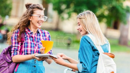 side view of smiling students with notebook standing on street