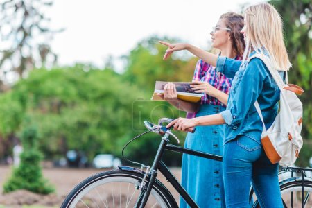 side view of young woman with bicycle pointing away with classmate near by on street