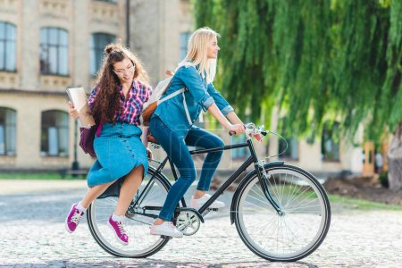 smiling young students riding bicycle together on street