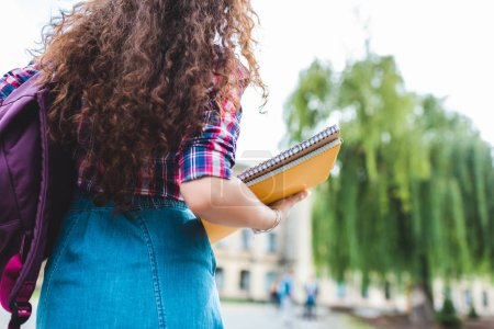 Photo pour Recadrée tir d'étudiant avec sac à dos et des cahiers sur la rue - image libre de droit