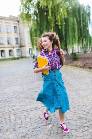 smiling student in eyeglasses with notebooks running on street