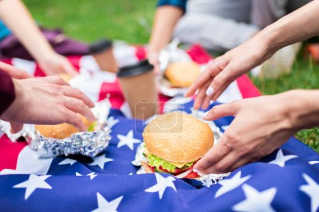 partial view of friends with burgers and american flag on green grass in park