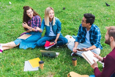 multiracial group of students with digital devices and notebooks sitting on green grass in park