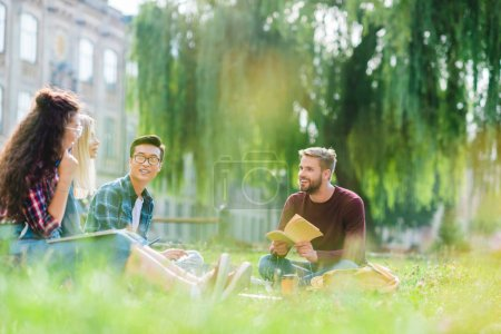 smiling multiracial students resting in park with university on background