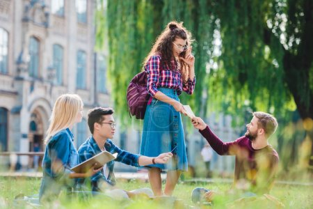 multiracial students studying in park with university on background