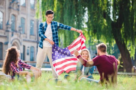 multicultural students with american flag in summer park