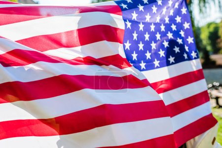 partial view of man holding american flag in hands in park