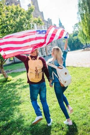 back view of couple with american flag holding hands in park