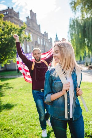 selective focus of smiling woman and boyfriend with american flag in hands in park
