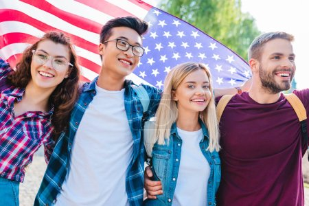 portrait of smiling multicultural students with american flag in park