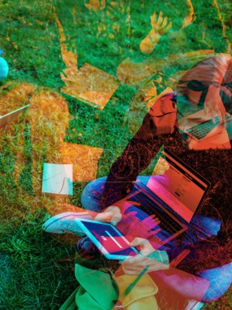 double exposure photo on student using tablet while sitting on green grass in park