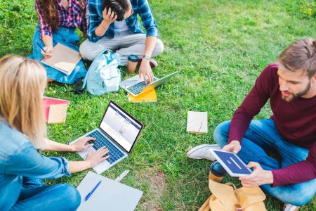 Photo for Partial view of multiethnic students with notebooks and digital devices sitting on green grass in park - Royalty Free Image
