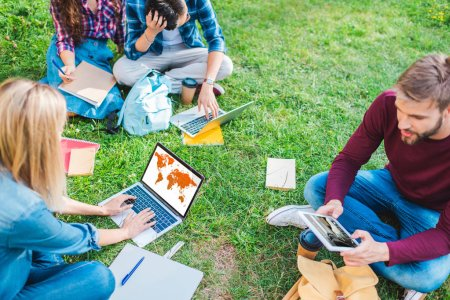 partial view of multiethnic students with notebooks and digital devices sitting on green grass in park