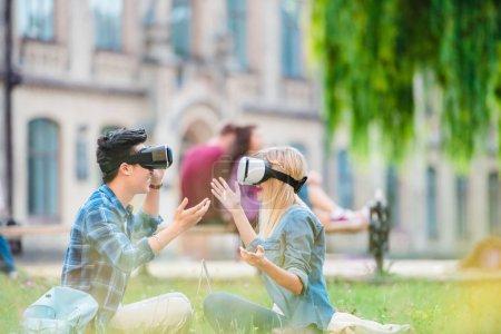 Foto de Vista lateral de estudiantes multiculturales en auriculares de realidad virtual con portátiles sentados en la hierba verde en el Parque - Imagen libre de derechos