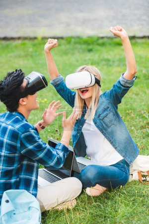Photo for Side view of multicultural students in virtual reality headsets with laptops sitting on green grass in park - Royalty Free Image