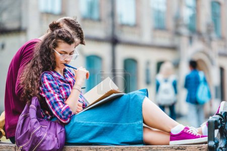 partial view of young woman with book and notebook leaning on boyfriend while studying on wooden bench in park