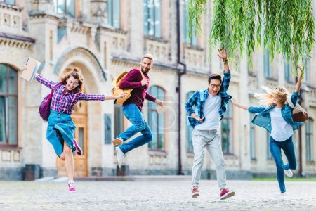 happy multicultural students with backpacks jumping on street with university on background