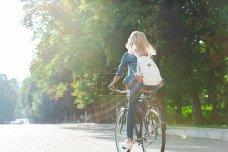 Photo for Back view of student with backpack riding bicycle on street - Royalty Free Image