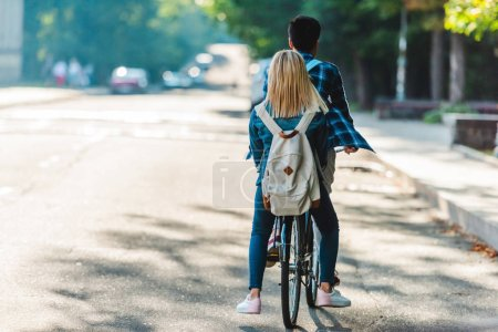 Photo for Back view of students riding bicycle together on street - Royalty Free Image