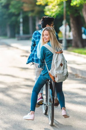 partial view of students riding bicycle together on street