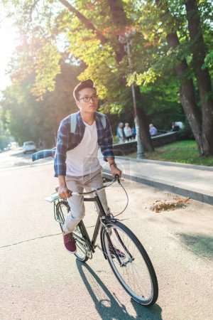 asian student in eyeglasses with backpack riding bicycle on street