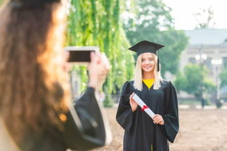 partial view of woman taking picture of smiling classmate during graduation near university