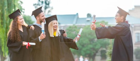 Photo for Portrait of happy multiracial graduates with diplomas on street - Royalty Free Image