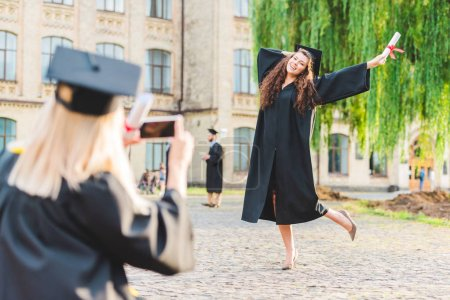 partial view of woman taking picture of classmate with diploma during graduation near university