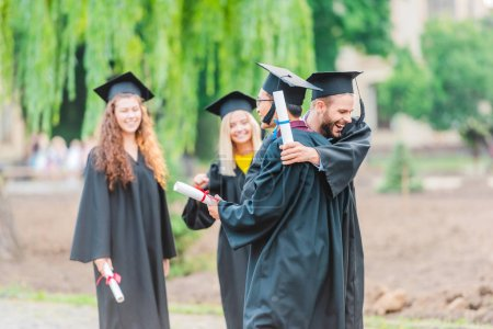 portrait of happy multiracial graduates with diplomas on street