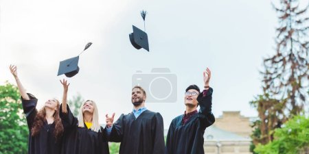 portrait of happy multicultural graduates throwing caps up in park
