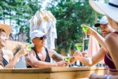 friends spending time together and drinking cocktails at swimming pool