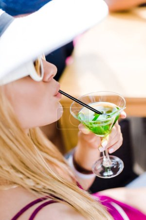 attractive girl drinking cocktail with straw