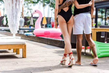 cropped image of boyfriend and girlfriend hugging and walking near swimming pool