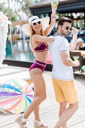 Photo for Couple posing with glasses of cocktails near swimming pool - Royalty Free Image