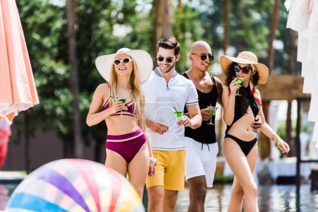 Photo for Four male and female friends walking near swimming pool with glasses of cocktails - Royalty Free Image
