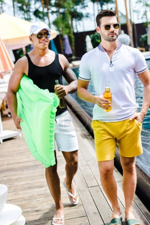 handsome male friends walking with inflatable mattress and beer near swimming pool