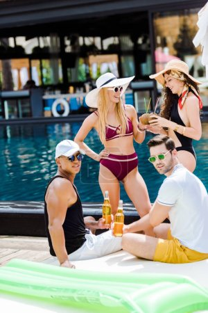 friends spending time near swimming pool with beer and coconut cocktails