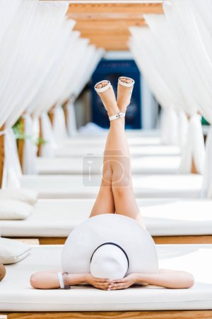 girl lying on sun lounger in white shoes and hat