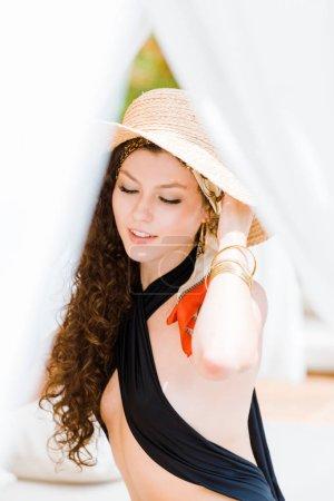 Portrait de jolie jeune fille avec des yeux fermés toucher chapeau