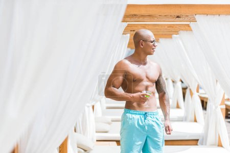 shirtless tattooed muscular man standing near sun loungers with cocktail