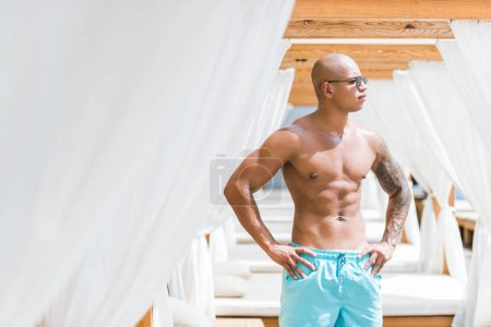 tattooed sportive man standing near sun loungers and looking away