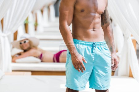 cropped image of shirtless boyfriend standing near sun loungers