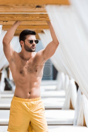 handsome shirtless man in sunglasses standing near sun loungers