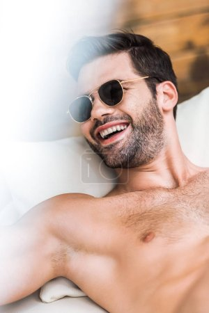 smiling handsome shirtless man in sunglasses lying on sun lounger