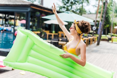 girl in swimsuit walking with inflatable mattress near swimming pool and waving hand