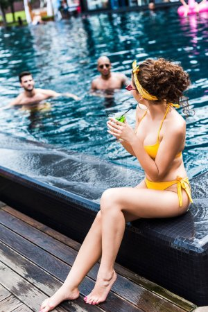 Photo for Girl sitting on poolside and drinking cocktail, male friends swimming in pool - Royalty Free Image